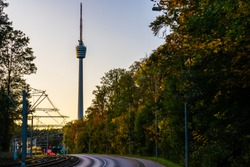 Germany, HDR of famous television tower stuttgart city next to a train and street with traffic decorated by colorful autumn foliage trees in autumn season