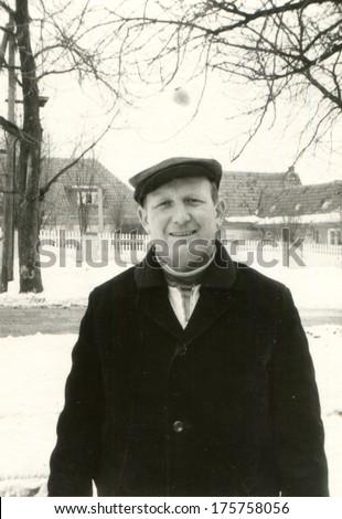 GERMANY, LEIPZIG - CIRCA 1960s: An antique photo of man posing on a snowy street