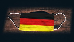 Germany National Flag at medical, surgical, protection mask on black wooden background. Coronavirus Covid–19, Prevent infection, illness or flu. State of Emergency, Lockdown