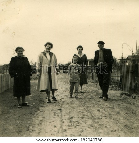 GERMANY, ROSTOCK - CIRCA 1950s: An antique photo of family posing on dirty road on the street