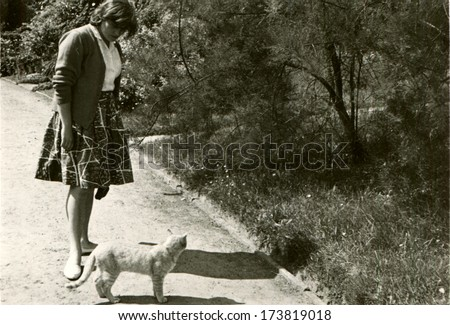 GERMANY, ROSTOCK - 1950s: An antique photo shows woman with cat on the footpath in the park