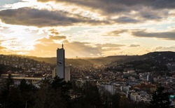 Germany, Stuttgart, Warm orange sunset sunlight and sunbeams shining on skyline of houses of stuttgart city from above