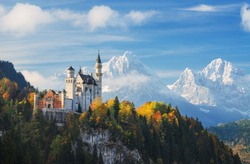 Germany. The famous Neuschwanstein Castle in the background of snowy mountains and trees with yellow and green leaves.