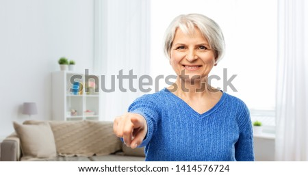 gesture, choice and old people concept - portrait of smiling senior woman in blue sweater pointing finger to you over home living room background