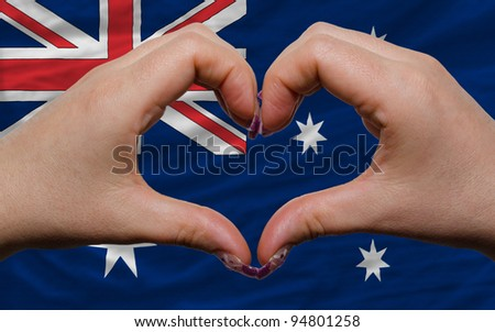 Gesture made by hands showing symbol of heart and love over national australia flag