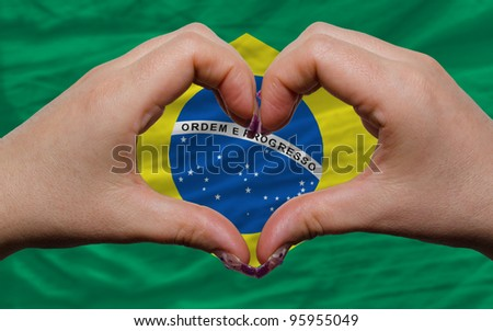 Gesture made by hands showing symbol of heart and love over national brazil flag