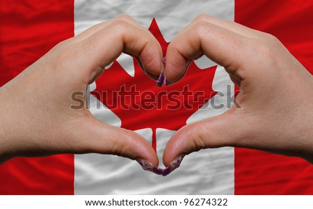 Gesture made by hands showing symbol of heart and love over national canada flag - stock photo