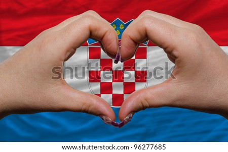 Gesture made by hands showing symbol of heart and love over national croatia flag