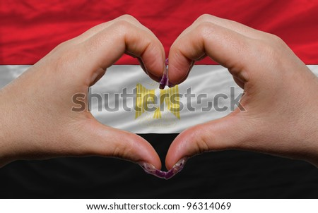 Gesture made by hands showing symbol of heart and love over national egypt flag