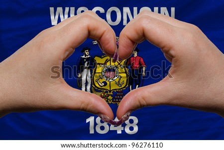 Gesture made by hands showing symbol of heart and love over us state flag of wisconsin