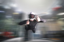 Gesture of approval. Fly men shows approval gesture by fingers. Sky diver in black suit. Teampleat skydiver.