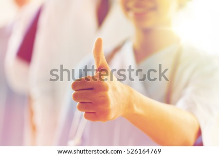 gesture, people, health care and medicine concept - close up of happy african female doctor or nurse showing thumbs up hand sign over group of medics meeting at hospital