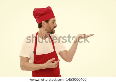Gesturing aside. Mature chief cook in red cooking apron. Senior cook with beard and moustache wearing bib apron. Bearded mature man in chef hat and apron. Presenting product, copy space. #1453000400