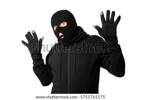 Photo of  Get Caught Concept. Portrait of thief in black balaclava and gloves raising hands up, isolated over white studio background