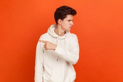 Get out! Profile portrait of serious angry teenager in casual white sweater with hood pointing finger, sneak male blaming another people. Indoor studio shot isolated on orange background