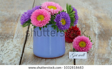 Get well card with colorful daisies in blue vase on rustic wooden surface  #1032818683
