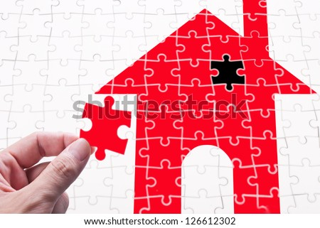 Get your house concept. Finish the goal of own a house. human hand with puzzle piece