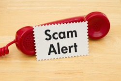 Getting a call that is an scam, A retro red phone with note card on a desk with text Scam Alert