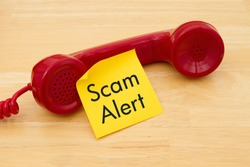 Getting a call that is an scam, A retro red phone with yellow sticky note on a desk with text Scam Alert