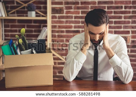 Shutterstock Getting fired. Handsome businessman in suit is sitting sadly at the table in office near the box with his stuff