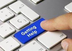 Getting Help Written on Blue Key of Metallic Keyboard. Finger pressing key.