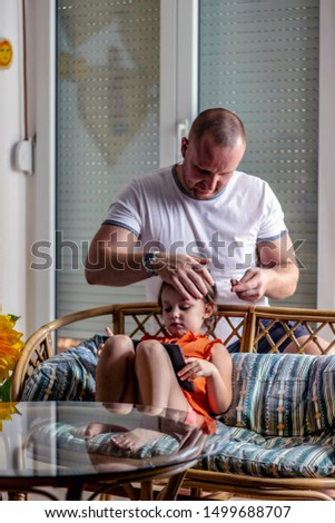 Getting ready for kindergarten. Young father making hairstyle for beautiful daughter in orange dress. Father and daughter bonding. Caring cheerful father in white shirt fixing hair slide on her hair.  #1499688707