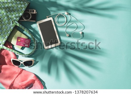 Getting ready for summer beach vacations: full bag with tablet, credit card and fashion accessories, travel and leisure concept #1378207634