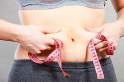 Getting rid of belly fat, diet, weight loss or gain concept. Woman touching stomach holding measuring tape