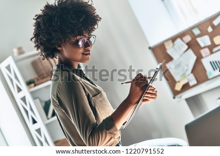 Getting things done. Attractive young African woman writing something down while working in the office                     #1220791552