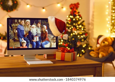 Getting together with your loving family is the best gift. Computer with photo of happy parents and children reunited for Christmas set as desktop background standing on desk in cozy room