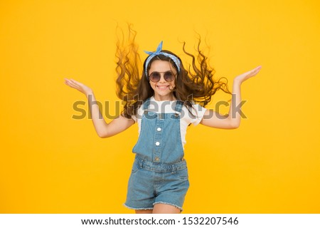 Getting your hairstyle to last all day. Happy child with curly hairstyle flying on yellow background. Small cute girl smiling with long wavy hairstyle. Fashion look of hairstyle with glamorous curls.