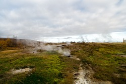 Geyser natural miracle. Steam of hot mineral source in Iceland. Iceland famous for geysers. Iceland geyser park. Landscape meadow with clouds of steam. Geysir hot spring area. Highly active geyser.
