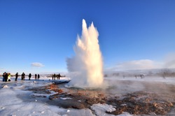 Geyser Park in Iceland. Stokkur eruption with sunstar in a beautiful sunny day in winter.