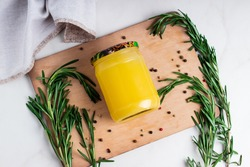 Ghee clarified butter desi in glass jar with rosemary on natural wooden background.