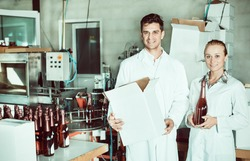 Gheerful man and woman winery workers holding carton package with wine bottles on the winery factory. Focus on both persons