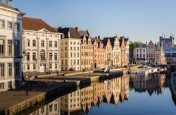 Ghent, Belgium. Sunrise in historical center of Ghent with medieval buildings of Korenlei, Graslei and castle of the counts (Gravensteen) reflecting in water of river Leie in Ghent, Flanders, Belgium.