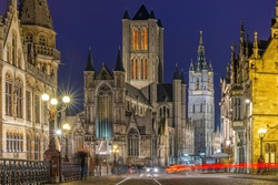 Ghent (Gent) city center at night with blurred motion of people and transportation vehicles with Saint Bavo Cathedral and belfry, East Flanders, Belgium.