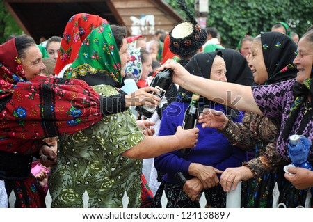 GHERTA MICA, ROMANIA - JULY 12: Unidentified villagers in traditional dresses celebrate a traditional Romanian wedding on JULY 12, 2012, in Gherta Mica, Maramures, Romania.