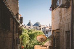 ghetto back street foreground urban landmark view with abandoned rust TV antenna of Jerusalem old city with religion cathedral dome on background