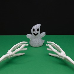 Ghost from Halloween and the bones of the hands that want to catch her on a green-black background. Minimal scene concept.