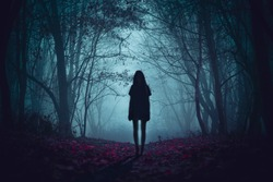 Ghost on the scary road in the paranormal world. Horrible dream. Strange forest in a fog. Mystical atmosphere. Dark wood. Mysterious road. Gothic witch. Background wallpaper. Gloomy times.