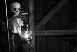 Ghost tours, Droitwich Spa, Worcester, England, United Kingdom, 02/10/2019, Ghost Tours, Skeleton holding a lit oil lamp against a wooden structure at night. Halloween, Ghost stories and Ghost tours.