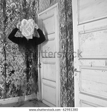 Ghostly figure fading into textured peeling wall surface.