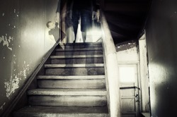 Ghostly figure standing on stairs holding doll