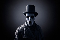 Ghostly figure with extra tall black vintage top hat in the dark