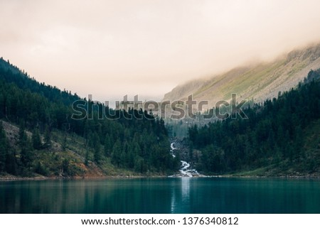Ghostly forest near mountain lake in early morning. Mountain creek flows into lake. Ripple on smooth water surface. Low clouds. Dark calm atmospheric misty woodland landscape. Tranquil atmosphere. #1376340812