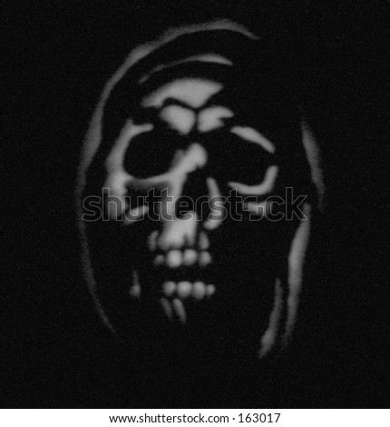 Ghostly image in grey, carved Halloween pumpkin