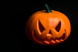 Ghostly isolated plastic Halloween orange pumpkin with scary face on black background with copy space