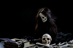 Ghostly skull typing something on table on black background. Ghost using Typewriter text with paper message on isolated. Halloween concept.
