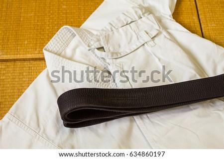 Gi ( martial arts uniform for Karate, Judo, Jiu-Jitsu, Kenpo, taekwondo) and black belt on Tatami ( Japanese straw floor covering ) #634860197